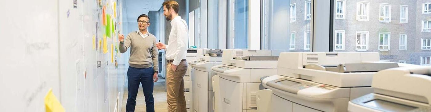 two men working together to solve a problem with printers in the foreground